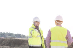 Male engineer using mobile phone while standing with colleague at construction site against clear sky Stock Images