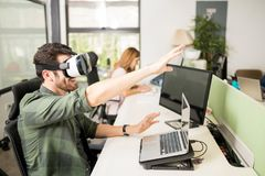 Computer programmer using VR glasses. Male engineer using virtual reality glasses in office with coworker in background Royalty Free Stock Image