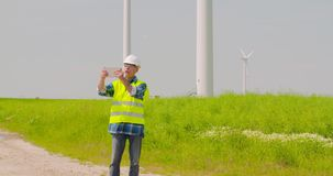 Male engineer video conferencing against windmills. Lockdown shot of confident mature male engineer video conferencing and pointing at windmills while standing stock video