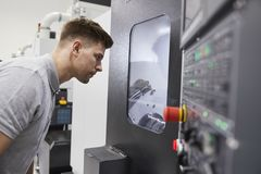 Male Engineer Watching Progress Of CNC Machinery In Factory royalty free stock photo