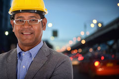 Male engineer wear yellow helmet with city light background. Male engineer wear a yellow helmet with city light background Royalty Free Stock Photos