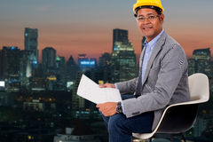 Male engineer wear yellow helmet with city light background. Male engineer wear a yellow helmet with city light background Stock Photography