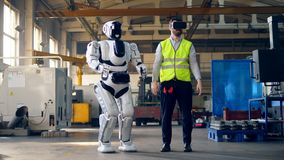 Male engineer wears VR glasses and controls a cyborg. stock video footage