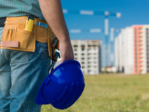Male engineer at work. Closeup of male engineer holding blue hardhat, with buildings in construction on background Royalty Free Stock Photos