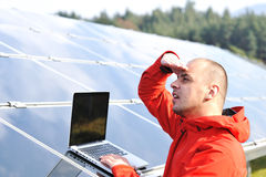 Male engineer at work place. Solar panels in background Royalty Free Stock Photography
