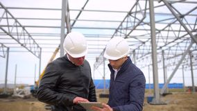 Male engineers construction supervisors in hard hats working and discussing plan. They checking quality of object on. Construction site. Businessman engineer stock video footage