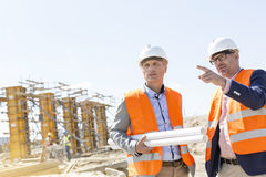 Male engineers discussing at construction site against clear sky Stock Photos