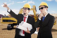Male engineers with excavator and blueprint Stock Photo