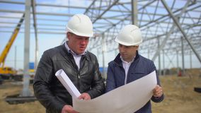 Male engineers supervisors in hard hats working with drawing blueprint and discussing plan, checking quality of object. On construction site. Businessman stock video footage