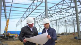 Male engineers supervisors in hard hats working with drawing blueprint and discussing plan. They checking quality of. Object on construction site. Businessman stock video