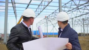 Male engineers supervisors in hard hats working with drawing blueprint and discussing plan. They checking quality of. Object on construction site. Businessman stock video footage