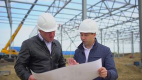 Male engineers supervisors in hard hats working with drawing blueprint and discussing plan. They checking quality of. Object on construction site. Businessman stock footage