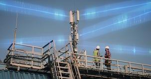 Male engineers talking near transmitting tower
