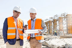 Male engineers using mobile phone at construction site against clear sky Royalty Free Stock Photos