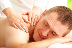Male enjoying massage treatment. With female hands on his shoulder and back Stock Image