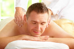 Male enjoying massage treatment. With female hands on his shoulder and back Stock Images