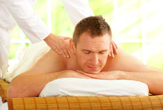 Male enjoying massage treatment. With female hands on his shoulder and back Stock Photography
