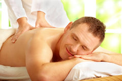 Male enjoying massage treatment. With female hands on his back Stock Images