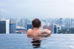 Male enjoying the view from infinity pool Royalty Free Stock Photography