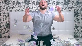 Male enjoys tremendous wealth. Man throws up a lot of banknotes on a white bed, throws money.  stock video footage
