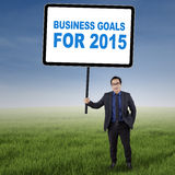Male entrepreneur with business goals for 2015. Asian businessman standing on the meadow while holding a board with number 2015 Royalty Free Stock Images