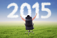 Male entrepreneur on chair with number 2015 Stock Photography