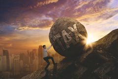 Male entrepreneur pushing word of tax. Male entrepreneur climbing on the cliff while pushing a stone with word of tax. Shot at sunrise time Royalty Free Stock Photo