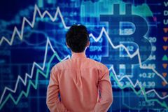 Male entrepreneur with declining graph and bitcoin symbol. Back view of male entrepreneur looking at declining finance graph with symbol of bitcoin on the Royalty Free Stock Image