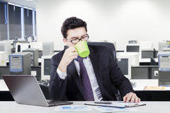 Male entrepreneur drinking coffee at workplace. Picture of a Caucasian businessman drinking a cup of coffee or tea while working with laptop in the office room Royalty Free Stock Photos