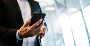 Male entrepreneur with mobile phone in office. Cropped image of male entrepreneur with cell phone in office. Focus on hands of businessman with smart phone royalty free stock photos