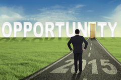 Male entrepreneur with an opportunity door. Young male worker standing on the road while looking at an opened opportunity door with number 2015 Stock Photography