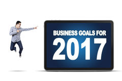 Male entrepreneur pointing at a billboard with text. Image of male entrepreneur jumping and pointing at a billboard with text of business goals for 2017 Stock Images