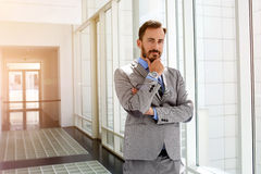 Male entrepreneur is pondering about something before meeting with important customers. Young man professional architect with thoughtful face is standing in Royalty Free Stock Images