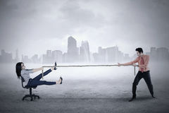 Male entrepreneur pulls his partner with rope Royalty Free Stock Photos