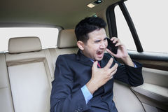 Male entrepreneur scold someone on the phone. Young entrepreneur sitting on the back side while scolding someone on the phone in the car Royalty Free Stock Images
