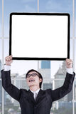 Male entrepreneur with signboard in office Royalty Free Stock Image