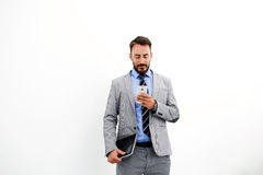 Male entrepreneur is standing against while wall background with copy space for your advertising content. Man intelligent lawyer with digital tablet in hand is Royalty Free Stock Image