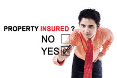 Male entrepreneur with text of property insured. Picture of male entrepreneur using a pen while selecting a yes option with a text of property insured Stock Photos
