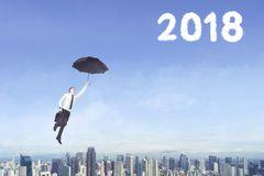 Male entrepreneur with umbrella and number 2018. Male entrepreneur using an umbrella to flying with clouds shaped numbers 2018 in the blue sky Stock Photos