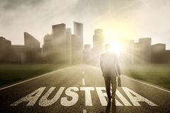 Male entrepreneur walking on the Austria word Stock Photo