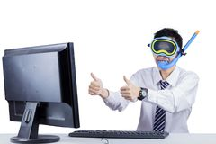 Funny businessman showing thumbs up on studio. Male entrepreneur wearing scuba mask while showing thumbs up in the studio, isolated on white background Royalty Free Stock Image