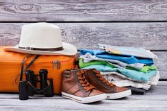 Male essentials for vacation. Clothes and accessories of tourist on wooden background Stock Images