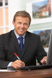 Male Estate Agent Working At Desk Royalty Free Stock Photography