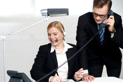 Male executive attending clients call. While female secretary enjoys the conversation Stock Image