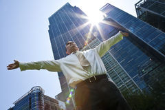 Male Executive In The City. A businessman with his arms out stretched messiah like in a modern city environment with the sun bursting over glass fronted office Royalty Free Stock Images