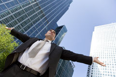 Male Executive In The City. A businessman with his arms out stretched messiah like in a modern city environment with the glass fronted office buildings Stock Images