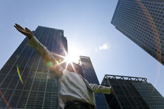 Male Executive In The City With Sunrise. A businessman with his arms out stretched messiah like in a modern city environment with the sun bursting over glass Stock Photography