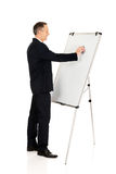 Male executive cleaning a flip chart Royalty Free Stock Photos