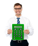 Male executive displaying green calculator Stock Image