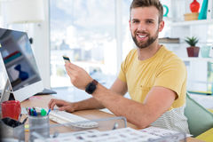 Male executive doing online shopping on computer at desk. In the office Stock Photos